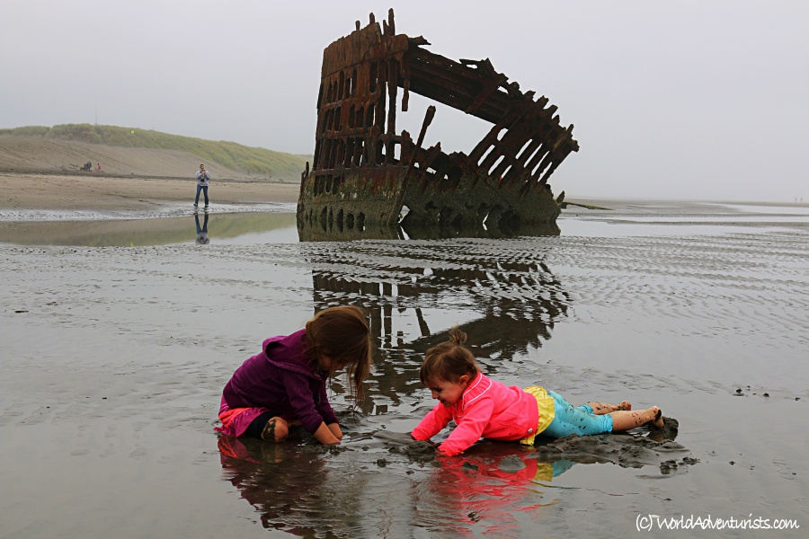 Kids playing in the sand in front of the wreck of the Peter Iredale