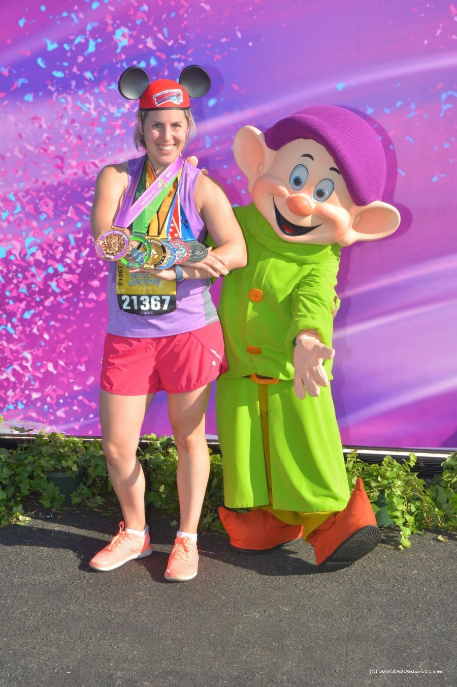 Girl displaying all the medals beside Dopey at the Dopey Challenge at Disney World