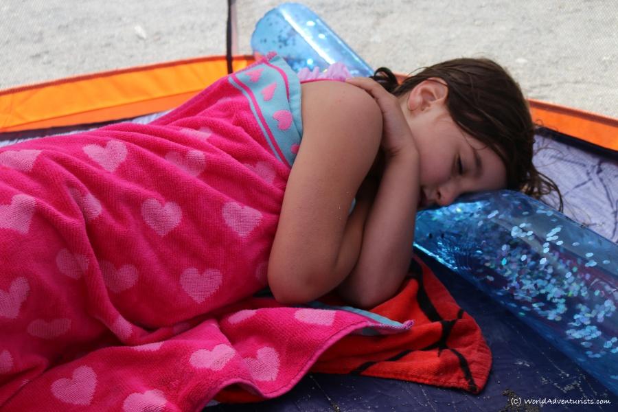 Little girl having a nap on the beach