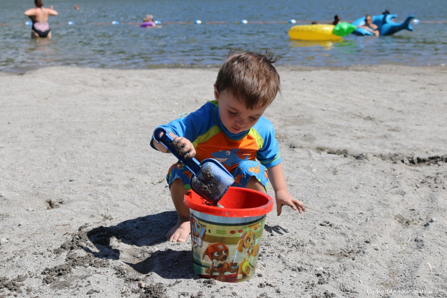 A little boy digging in the sand at Alice Lake in Squamish