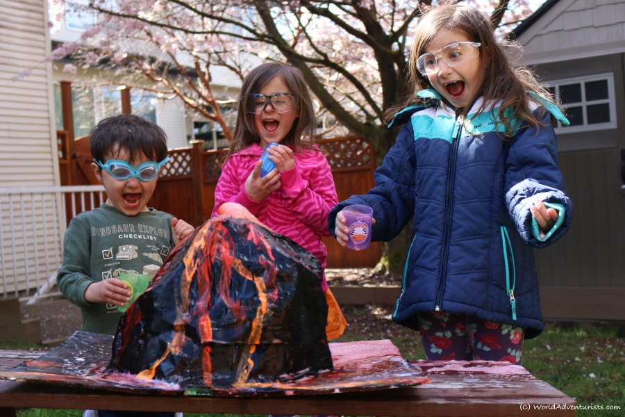 A paper mache volcano erupting with the kids having fun expressions
