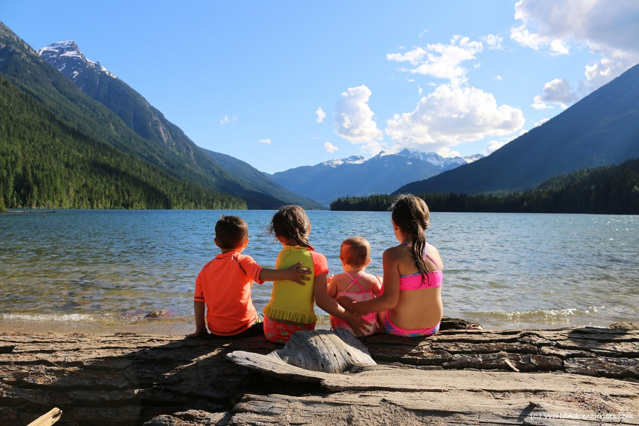 Four kids enjoying the views from sitting on a log together at Birkenhead Lake Provincial Park