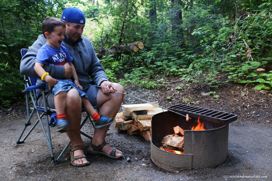 Father and son roasting a hot dog over a campfire