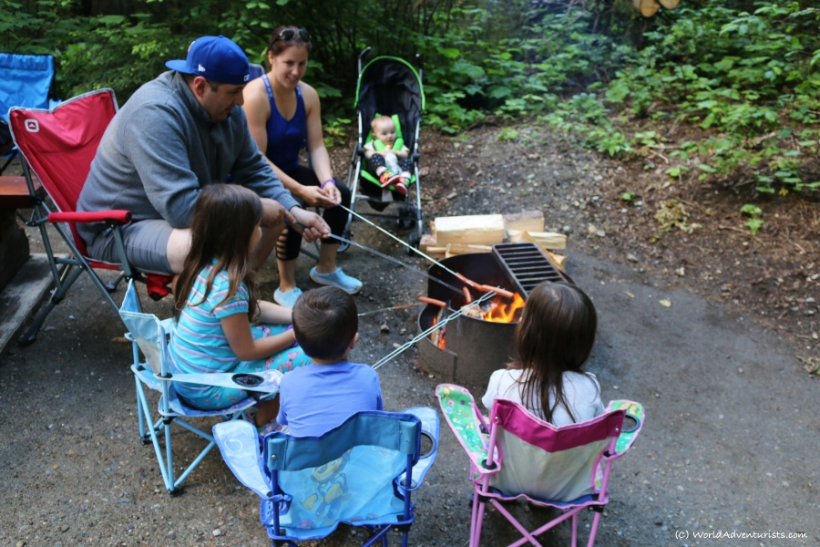 Family roasting hot dogs while camping at Wells Gray Provincial park