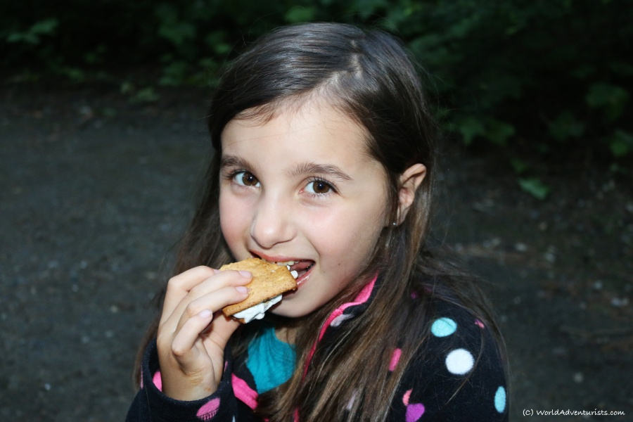 A young girl enjoying a s'more while camping